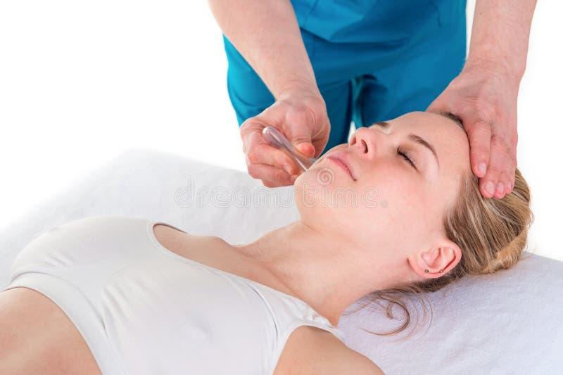 Fisioterapeuta de sexo masculino que da el masaje principal con una herramienta del lechón a fotografía de archivo