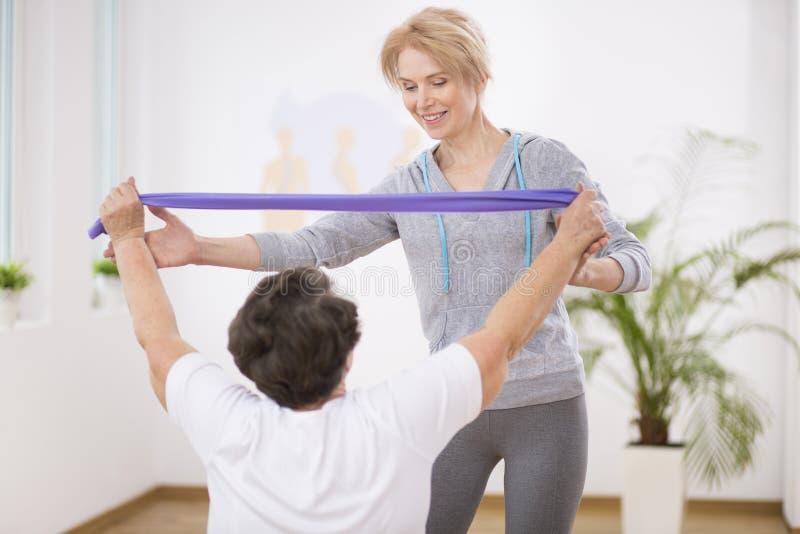 Fisioterapeuta de sorriso que ajuda a mulher superior que dá certo com faixas da resistência imagens de stock royalty free
