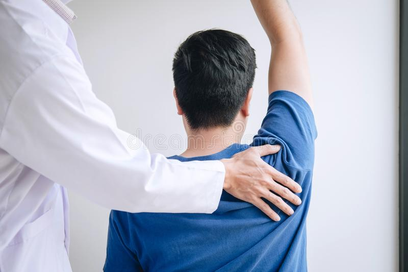 Fisioterapeuta del doctor que ayuda a un paciente masculino mientras que da ejercitando el tratamiento que da masajes al hombro d imagen de archivo