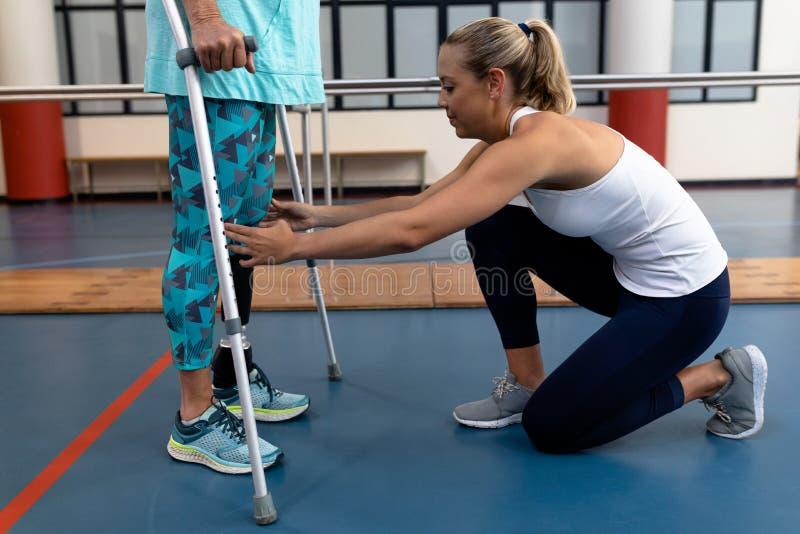 Fisioterapeuta fêmea que ajuda à caminhada superior deficiente da mulher com as muletas do cotovelo no centro de esportes foto de stock