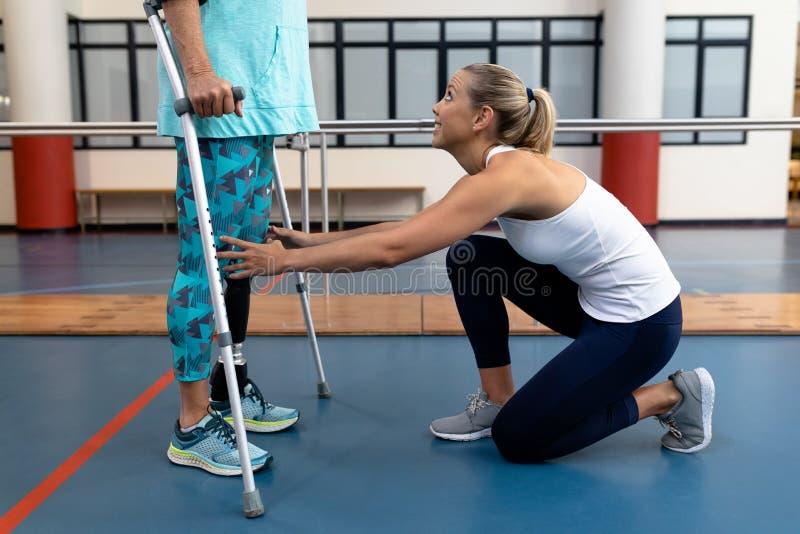 Fisioterapeuta fêmea que ajuda à caminhada superior deficiente da mulher com as muletas do cotovelo no centro de esportes fotografia de stock royalty free