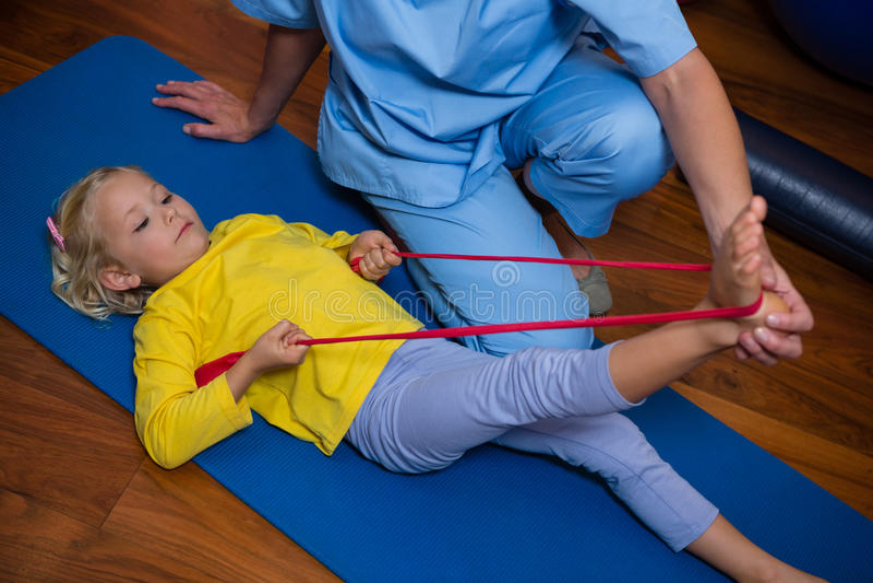 Fisioterapeuta fêmea que ajuda a um paciente da menina ao exercitar foto de stock royalty free