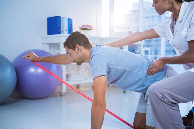 Fisioterapeuta fêmea que ajuda a um paciente masculino ao exercitar fotos de stock royalty free