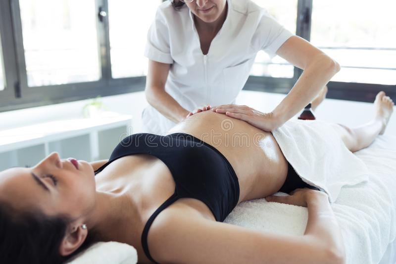 Fisioterapeuta fêmea que faz massagens a barriga na mulher gravida no centro dos termas imagem de stock royalty free
