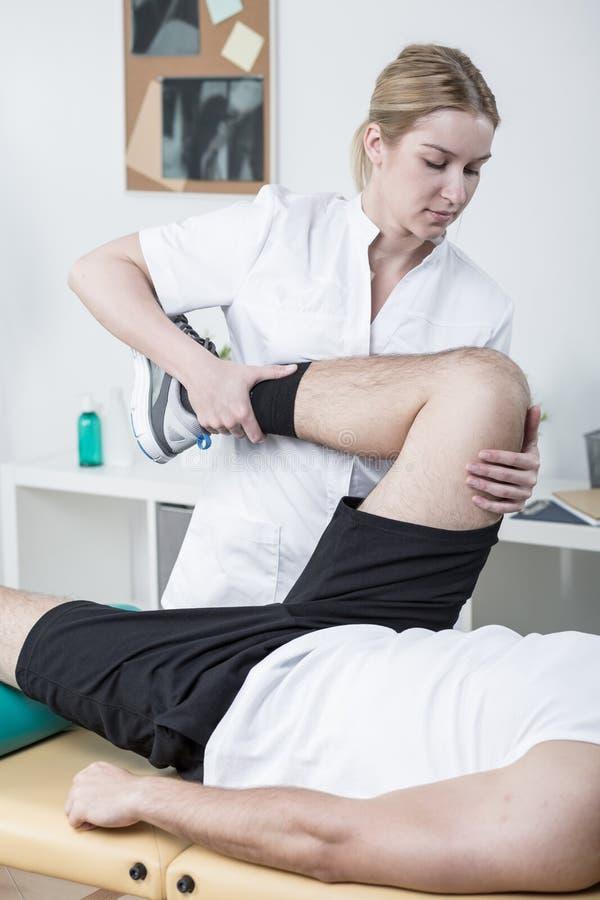 Fisioterapeuta fêmea que trabalha com paciente foto de stock
