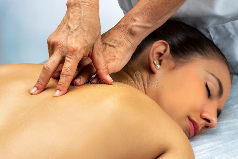 Fisioterapeuta fazendo massagem curativa nas costas ao longo da coluna na paciente fotografia de stock