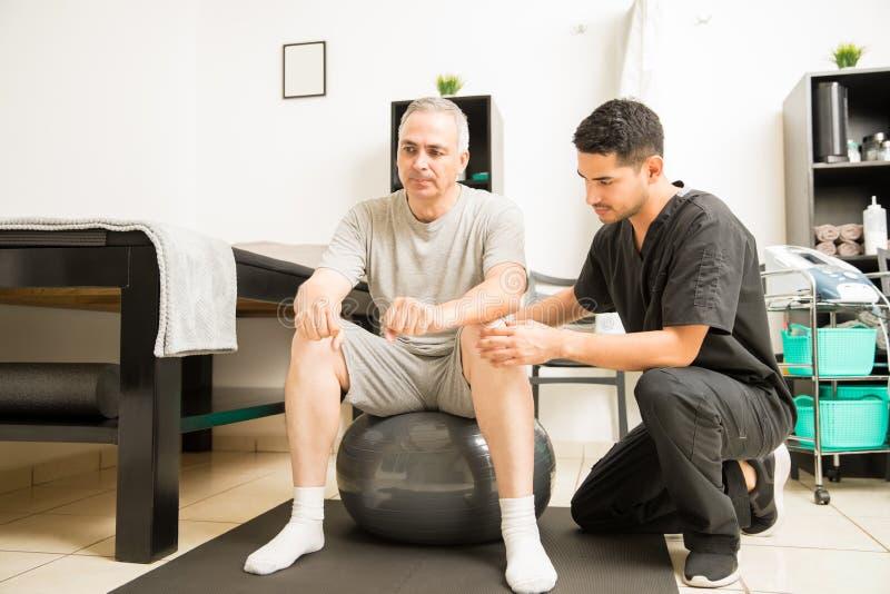 Fisioterapeuta Helping Patient Sitting en bola del ejercicio imagen de archivo libre de regalías