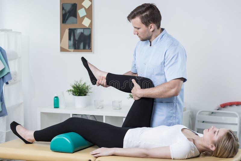 Fisioterapeuta masculino que exercita com paciente foto de stock