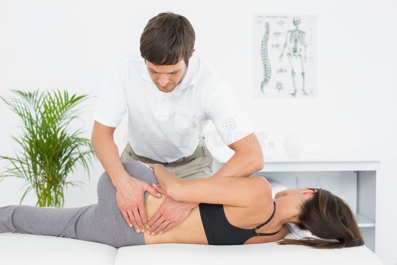 Fisioterapeuta masculino que faz massagens a parte traseira da mulher fotos de stock royalty free