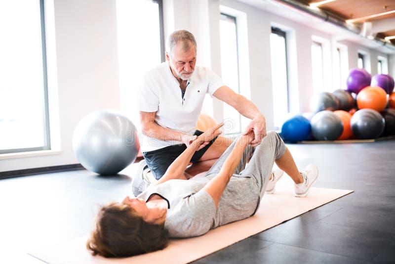 Fisioterapeuta mayor que trabaja con un paciente femenino imágenes de archivo libres de regalías