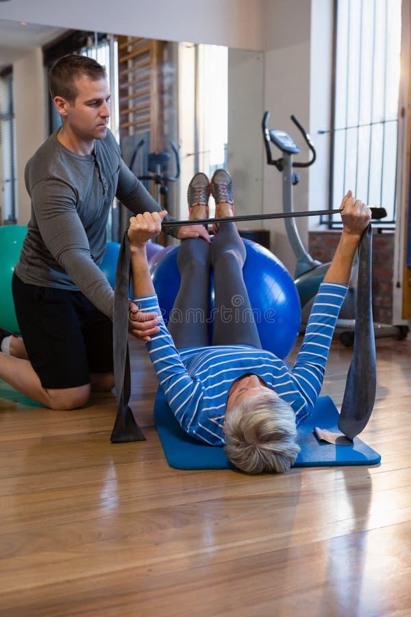 Fisioterapeuta que ajuda à mulher superior em executar o exercício com a faixa da resistência foto de stock royalty free
