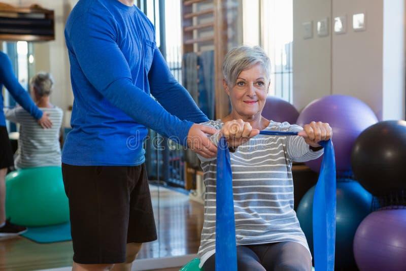 Fisioterapeuta que ajuda à mulher superior em executar o exercício de esticão com a faixa da resistência imagem de stock