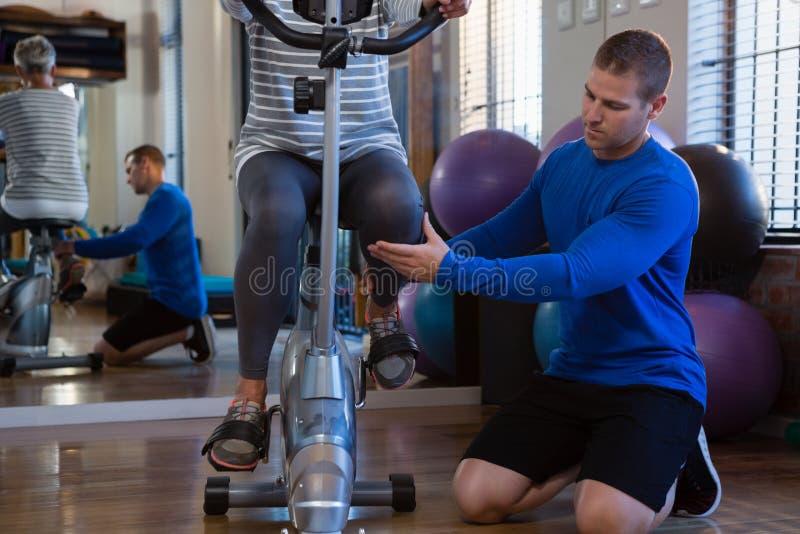 Fisioterapeuta que ajuda à mulher superior em executar o exercício na bicicleta de exercício fotos de stock