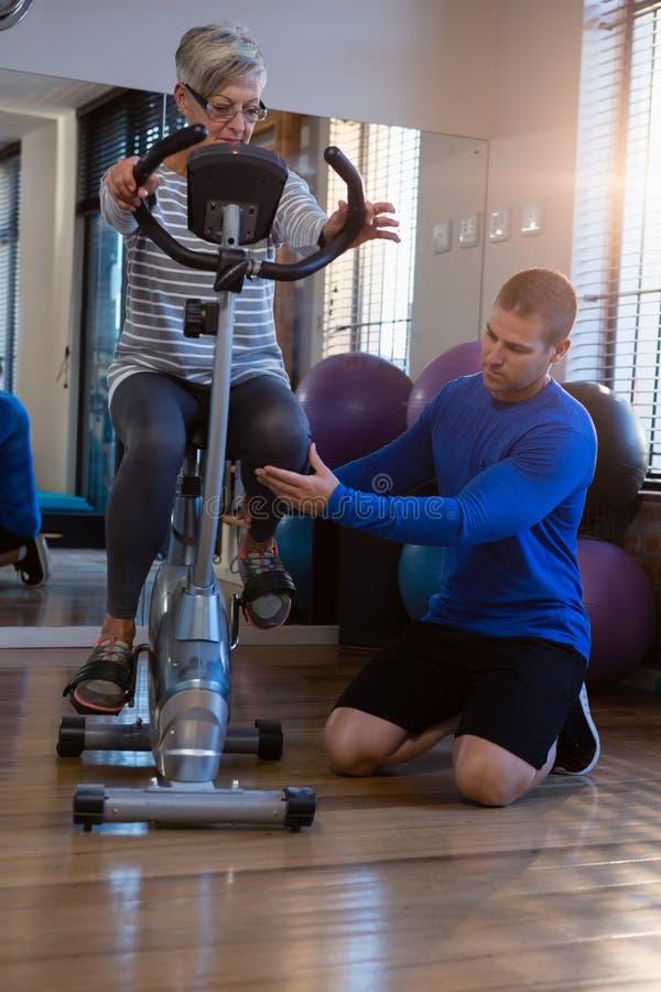 Fisioterapeuta que ajuda à mulher superior em executar o exercício na bicicleta de exercício foto de stock royalty free