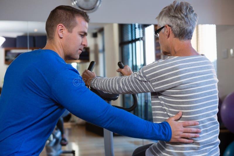 Fisioterapeuta que ajuda à mulher superior em executar o exercício na bicicleta de exercício imagens de stock