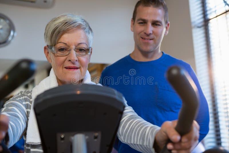 Fisioterapeuta que ajuda à mulher superior em executar o exercício na bicicleta de exercício imagem de stock royalty free