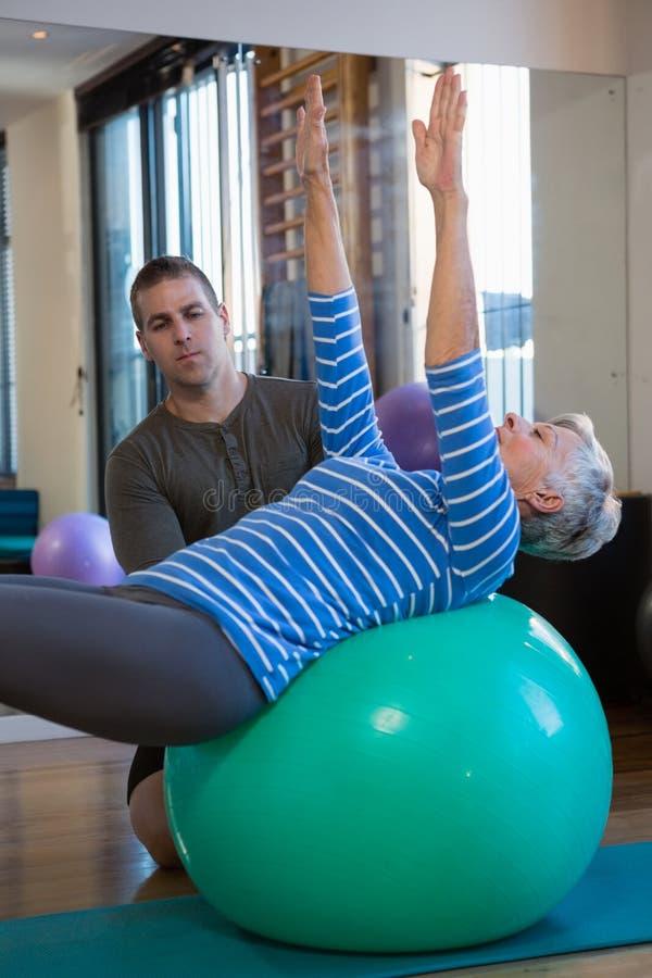 Fisioterapeuta que ajuda à mulher superior em executar o exercício na bola da aptidão foto de stock royalty free