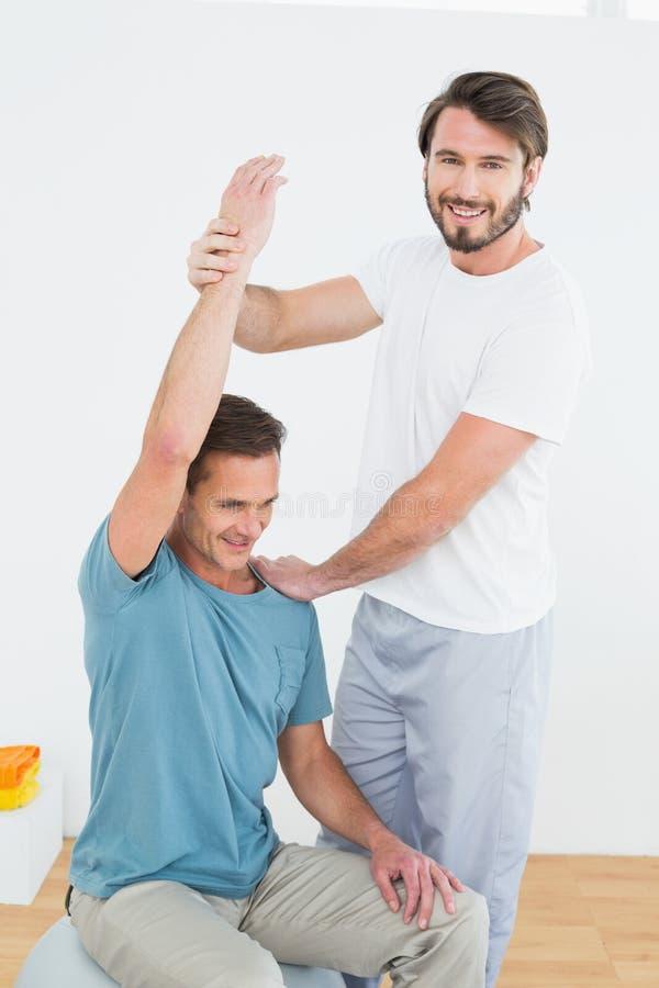 Fisioterapeuta que ajuda ao homem com esticão de exercícios foto de stock royalty free