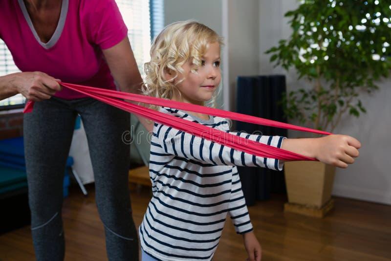 Fisioterapeuta que ajuda ao paciente da menina em executar o exercício de esticão com a faixa da resistência fotos de stock royalty free