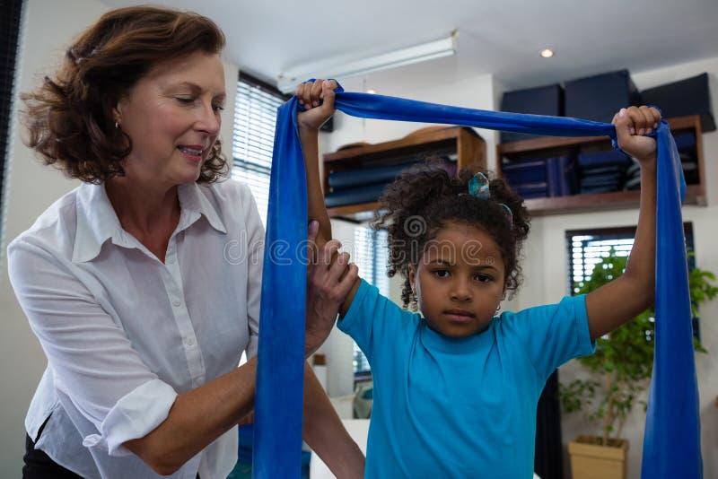 Fisioterapeuta que ajuda ao paciente da menina em executar o exercício de esticão da faixa da resistência fotografia de stock royalty free