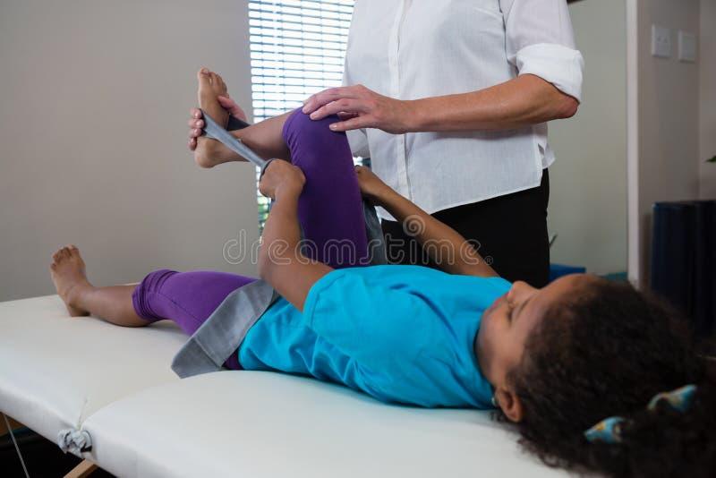 Fisioterapeuta que ajuda ao paciente da menina em executar o exercício de esticão da faixa da resistência foto de stock royalty free