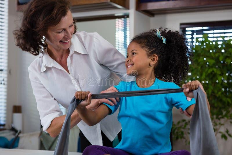 Fisioterapeuta que ajuda ao paciente da menina em executar o exercício de esticão da faixa da resistência imagem de stock royalty free