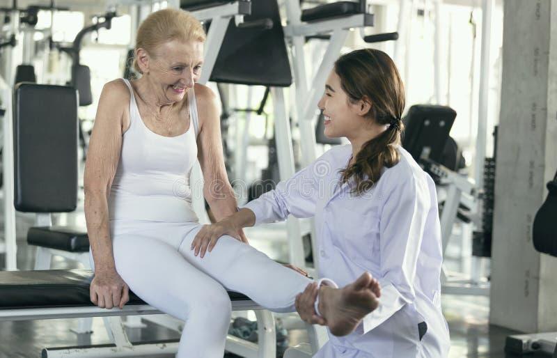 Fisioterapeuta que ajuda a mulher superior idosa no centro físico imagens de stock