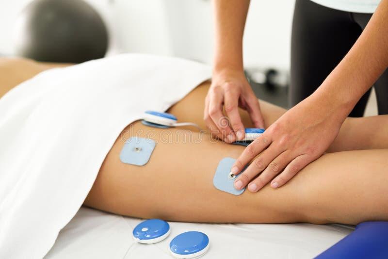 Fisioterapeuta que aplica el electro estímulo en terapia física imagen de archivo