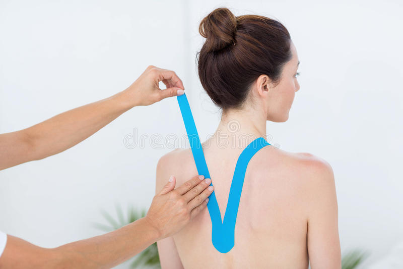 Fisioterapeuta que aplica a fita azul do kinesio aos pacientes para trás imagens de stock royalty free