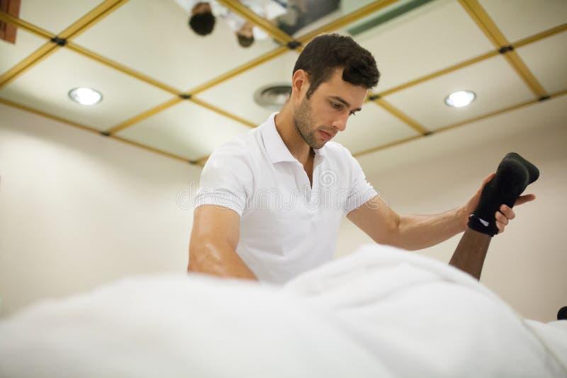 Fisioterapeuta que aplica masaje imágenes de archivo libres de regalías