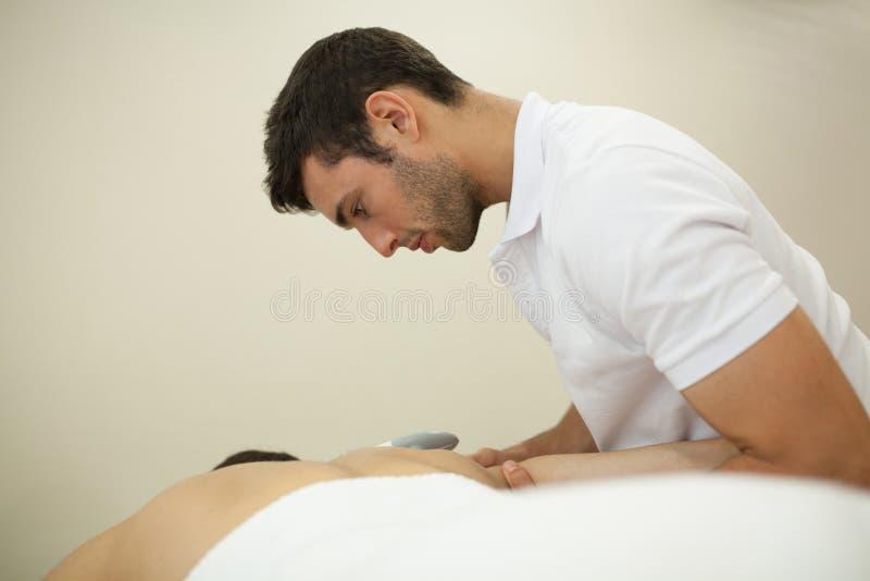 Fisioterapeuta que aplica a massagem imagem de stock royalty free