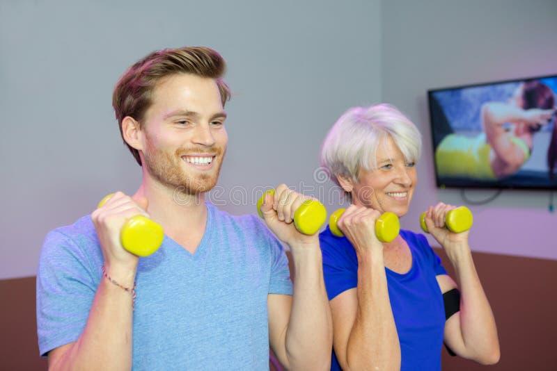 Fisioterapeuta que ayuda al mayor femenino para levantar pesa de gimnasia imagenes de archivo