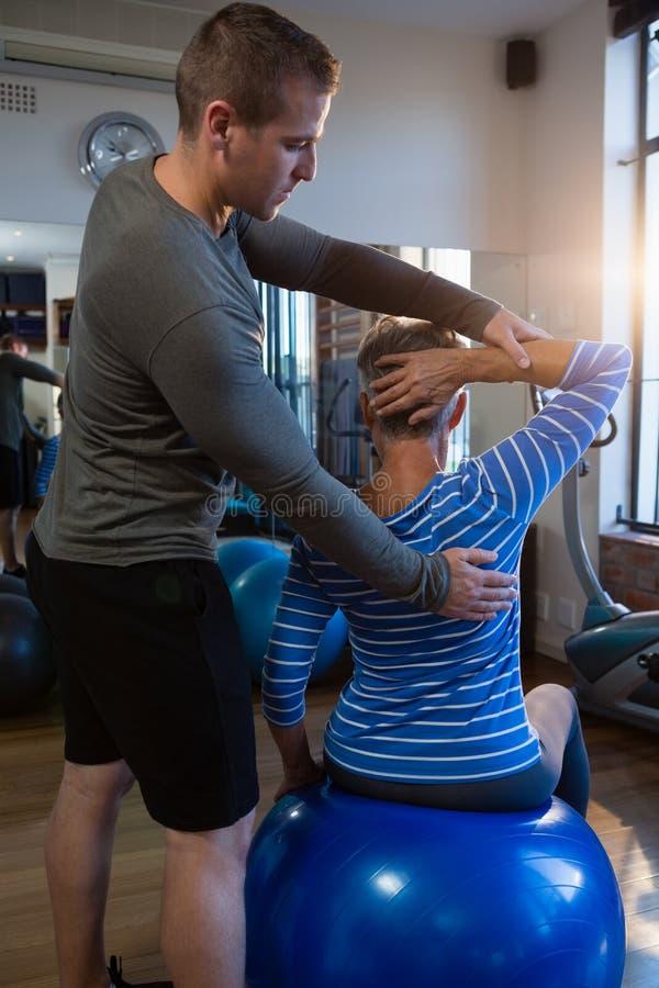 Fisioterapeuta que ayuda a la mujer mayor en ejercicio fotografía de archivo