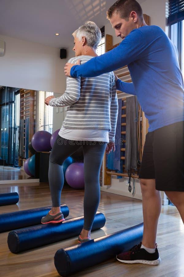 Fisioterapeuta que ayuda a la mujer mayor en la ejecución de ejercicio en el rollo de espuma fotos de archivo
