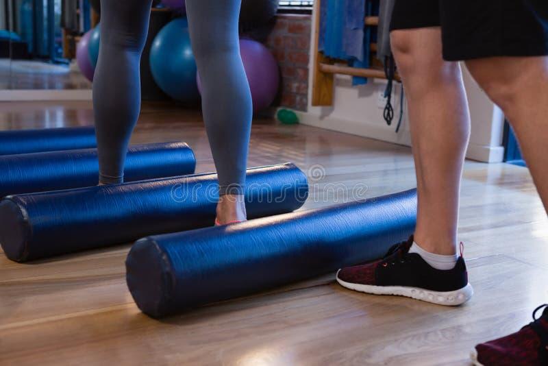 Fisioterapeuta que ayuda a la mujer mayor en la ejecución de ejercicio en el rollo de espuma fotografía de archivo