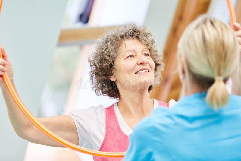 Fisioterapeuta que ayuda a la mujer mayor fotos de archivo libres de regalías