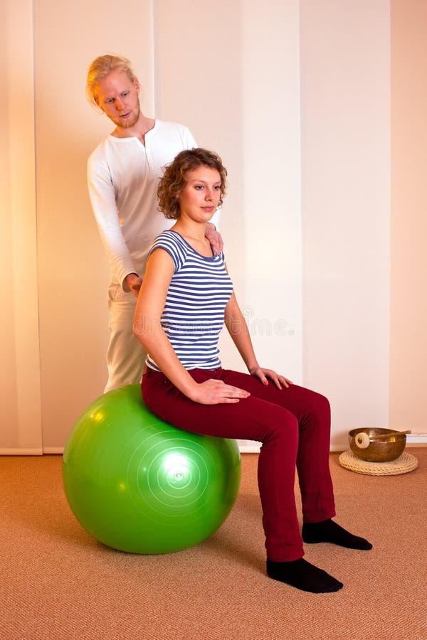 Fisioterapeuta que corrige, postura imagen de archivo