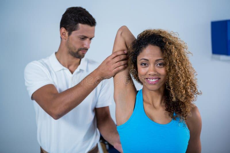 Fisioterapeuta que dá a massagem do braço ao paciente fêmea foto de stock royalty free
