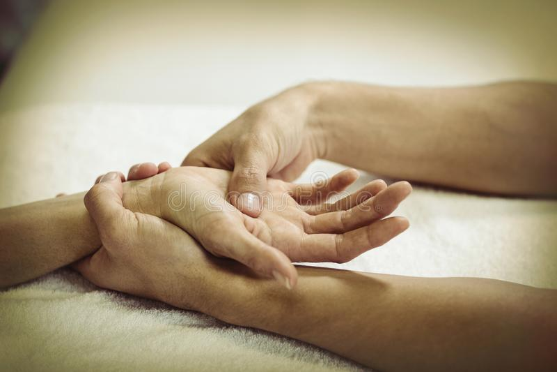 Fisioterapeuta que da masaje de la mano a una mujer fotos de archivo