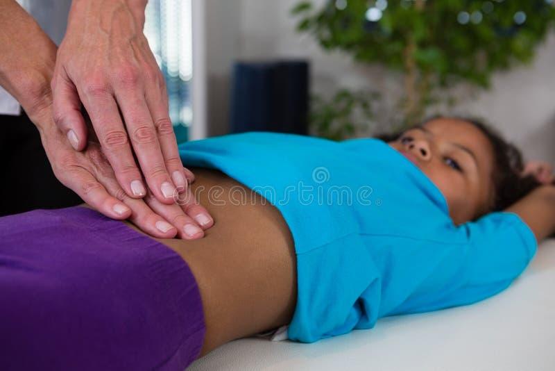 Fisioterapeuta que da masaje del abdomen al paciente de la muchacha imagen de archivo