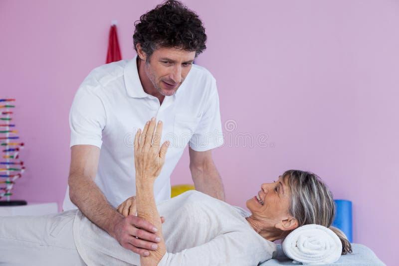 Fisioterapeuta que da masajes a la mano de una mujer mayor fotografía de archivo