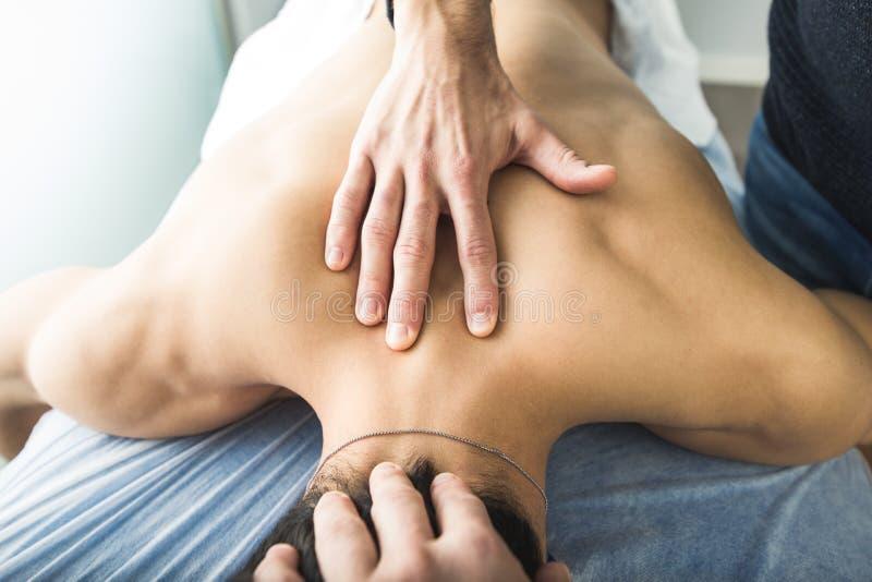 Fisioterapeuta que da masajes a la parte posterior y al cuello de un hombre joven Concepto de salud y de fisioterapia fotografía de archivo libre de regalías
