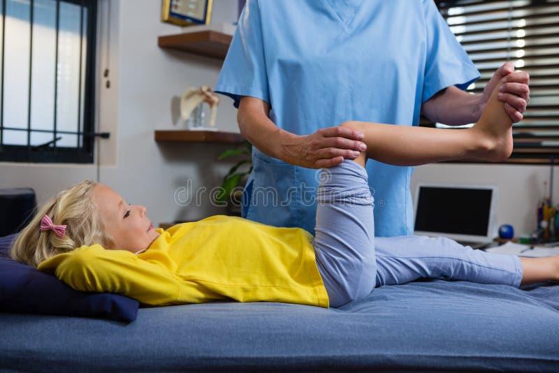 Fisioterapeuta que da terapia física a la muchacha imagen de archivo libre de regalías
