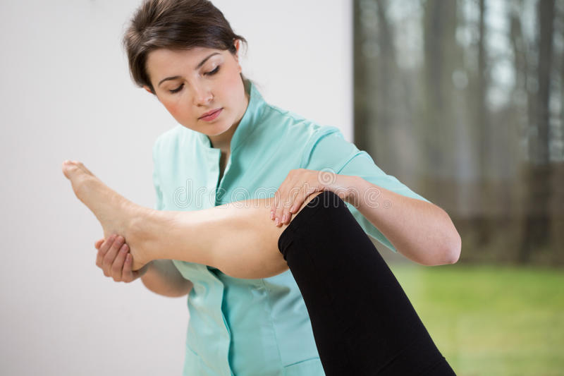 Fisioterapeuta que dobra o joelho imagens de stock