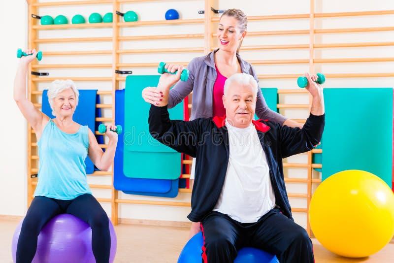 Fisioterapeuta que entrena a gente mayor foto de archivo