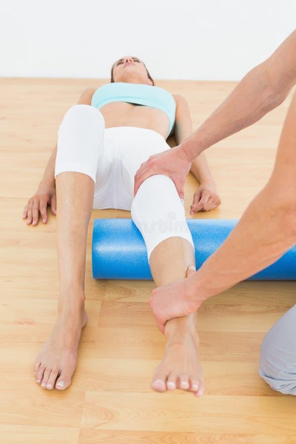Fisioterapeuta que examina o pé de uma jovem mulher imagens de stock royalty free