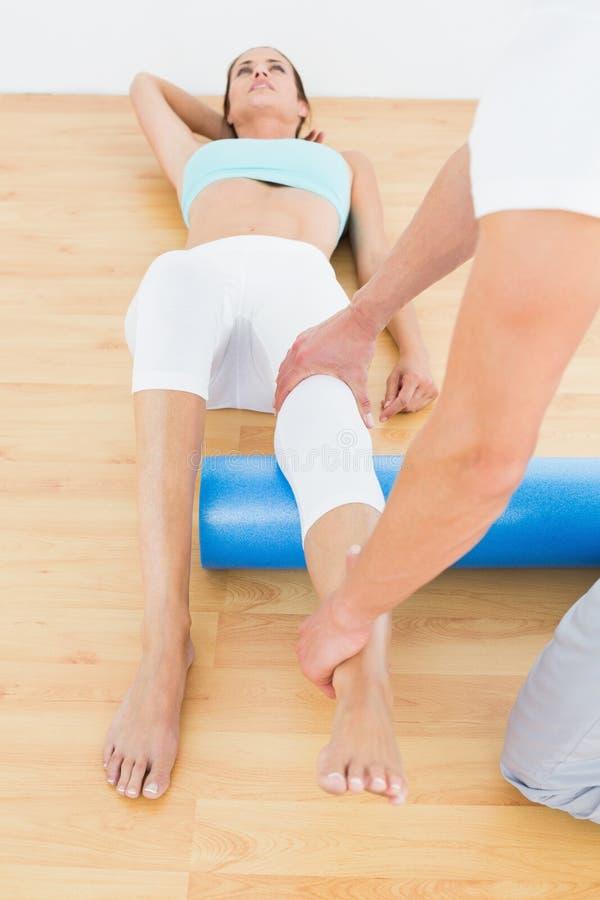 Fisioterapeuta que examina o pé de uma jovem mulher fotografia de stock