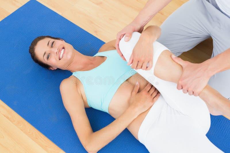 Fisioterapeuta que examina o pé de uma mulher feliz imagem de stock royalty free