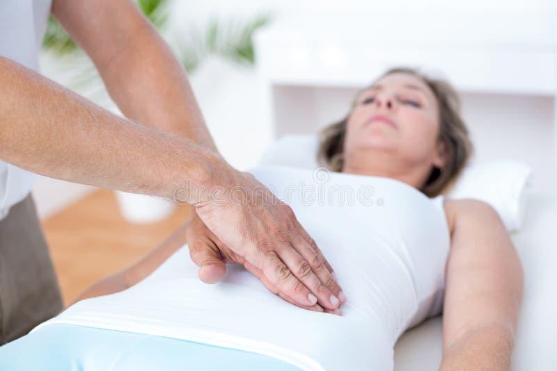 Fisioterapeuta que examina seu estômago dos pacientes foto de stock
