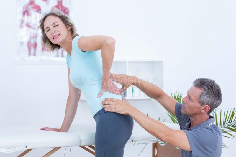 Fisioterapeuta que examina sua parte traseira do paciente fotografia de stock royalty free
